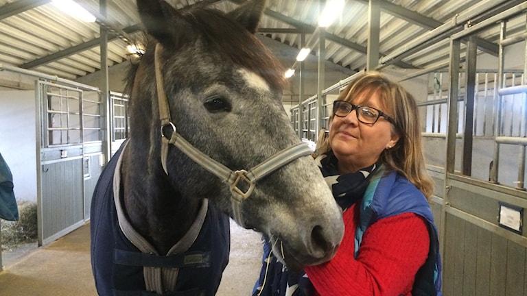 Elisabeth Flygt i stallet med en häst