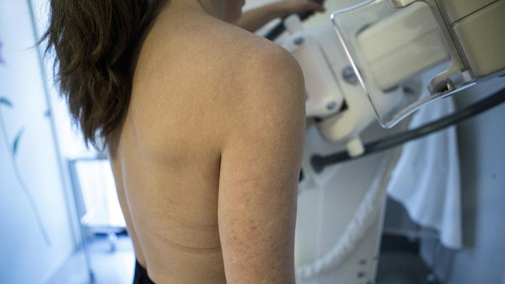 En kvinna står med ryggen mot kameran vid en röntgenkamera.
