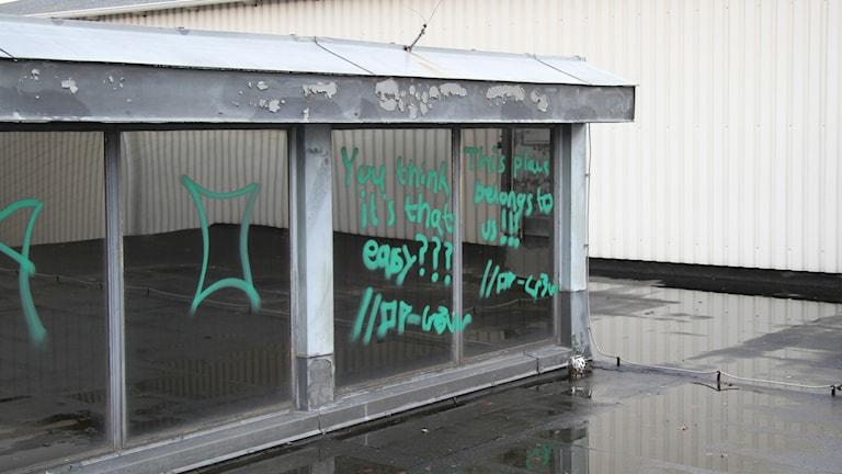 Klotter på fönster uppe på taket till Oscarsgymnasiet