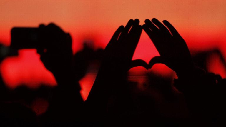 Händer i luften formar ett hjärta på en konsert