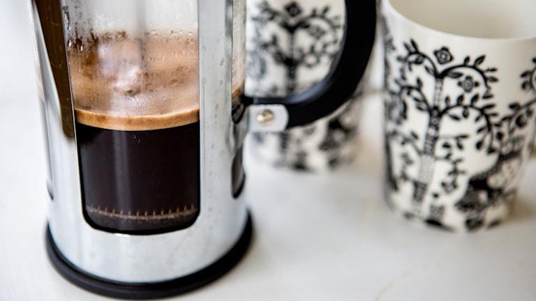 Kaffekanna bredvid muggar.