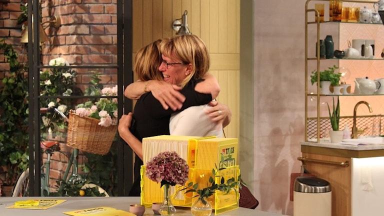 Två kvinnor som kramar varandra.