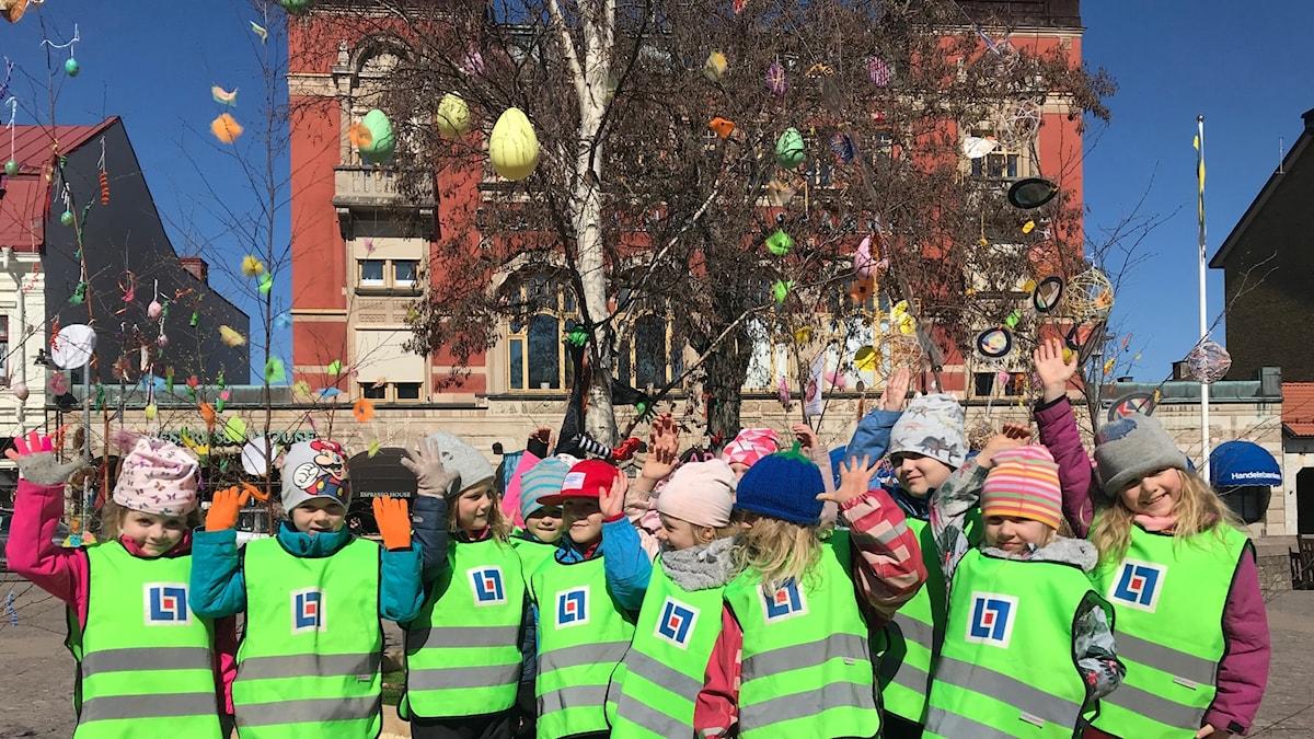 Barn i reflexvästar står framför träd.