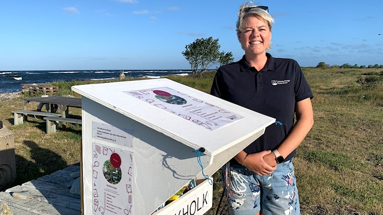 En kvinna står vid en vit bokholk vid havet.