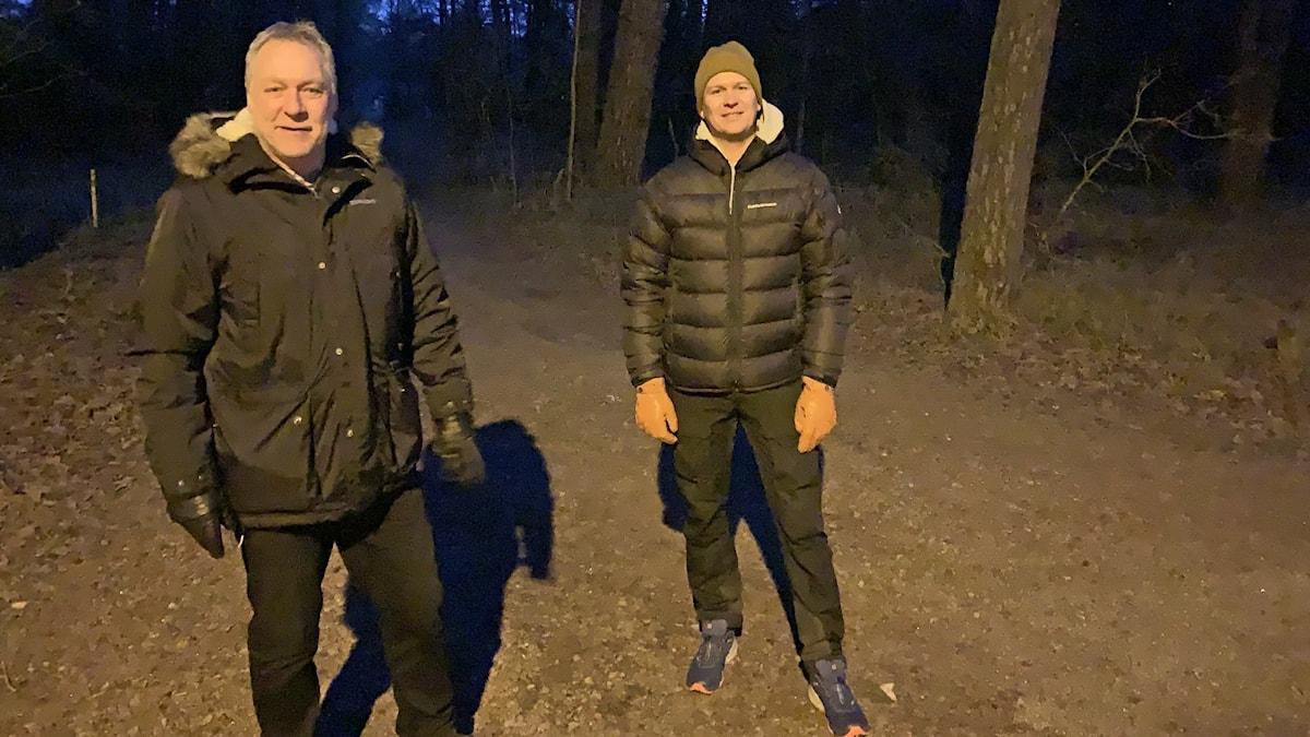 Två personer står i en tallskog.