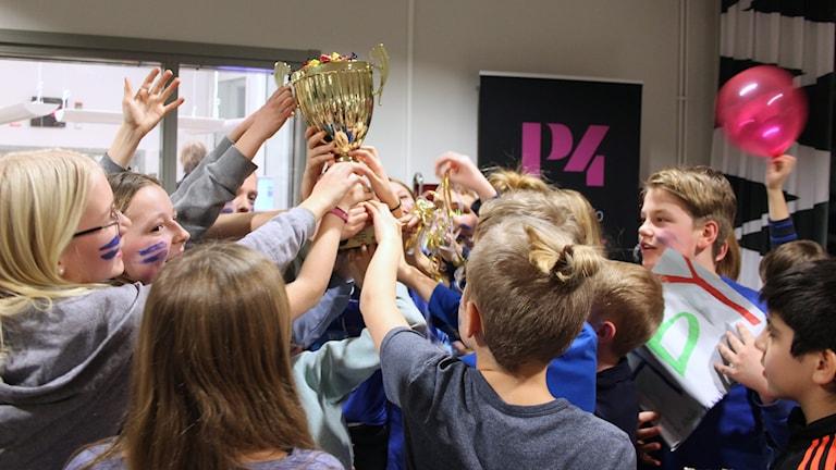 Åbyskolans elever lyfter en guldpokal.