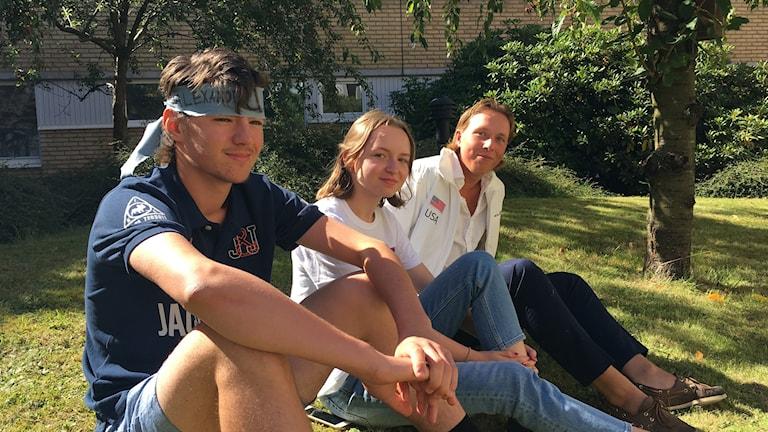 Gymanisieeleverna Alexander Schurmann, Olivia Ek, Gustav Haglund sitter i gräset.