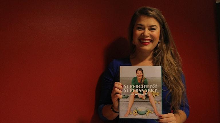 jessica Frej med sin bok, framör en  röd vägg. Jessica Frej har en kungsblå blus.