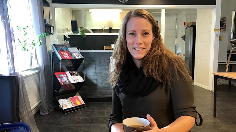 Kvinna sitter vid ett bord med en kaffekopp.