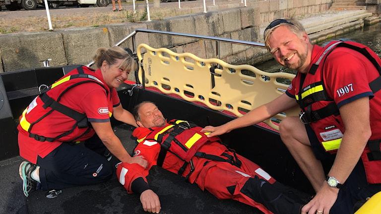 Övning: Man ligger på bår omgiven av sjöräddare