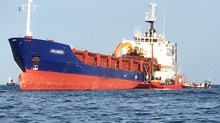 Tankbil på pråm intill fartyg på grund i vattnet.