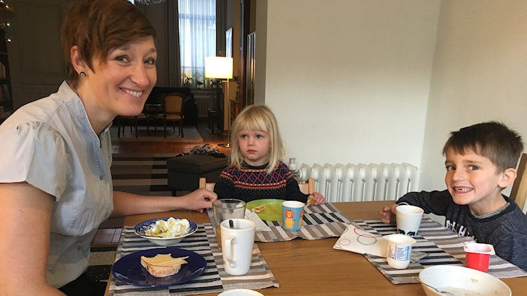 En kvinna sitter och äter frukost tillsammans med sin dotter och son.