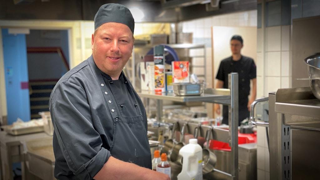 En man står i ett storkök och tittar mot kameran.