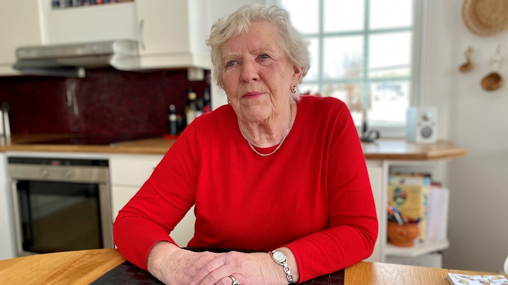 En äldre kvinna sitter vid ett köksbord.