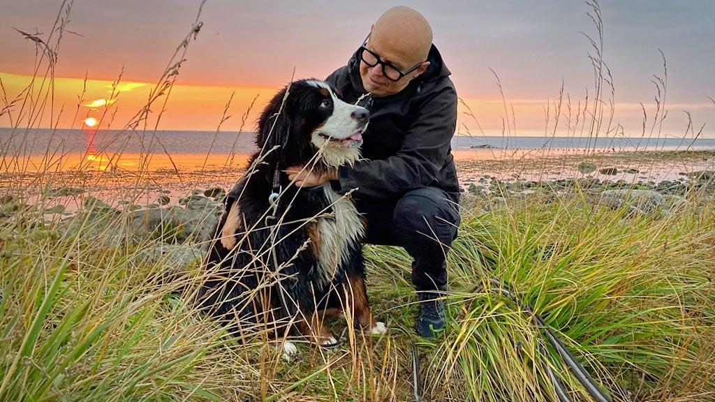 EN man och en hund sitter på stranden med en soluppgång i bakgrunden.