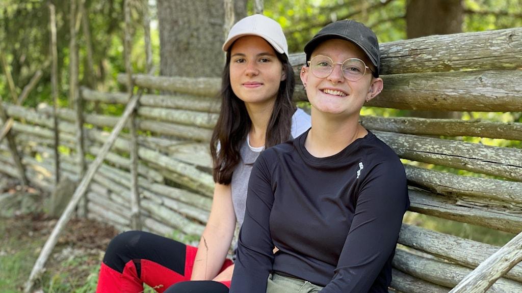 Två tjejer som lutar sig mot ett staket.