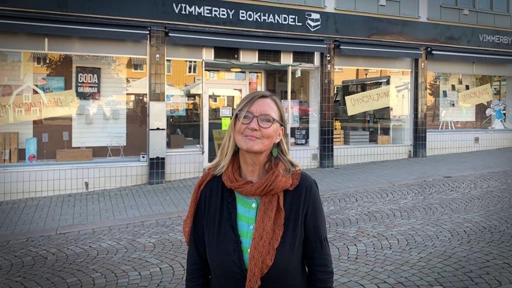 Kvinna står framför en bokhandel.