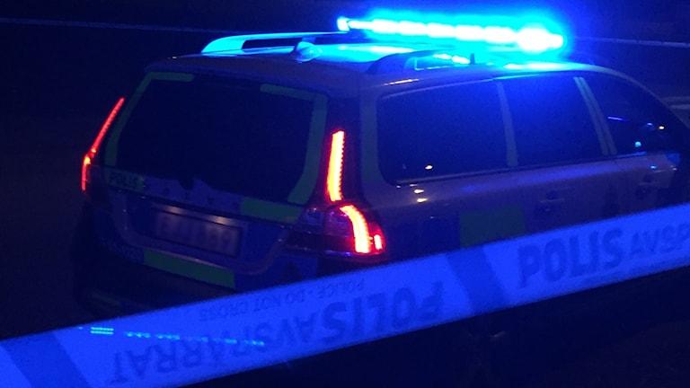 Polisbil och avspärrningsband.