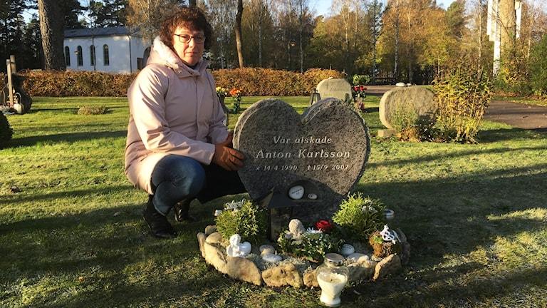 Kicki Karlsson sitter vid en grav.
