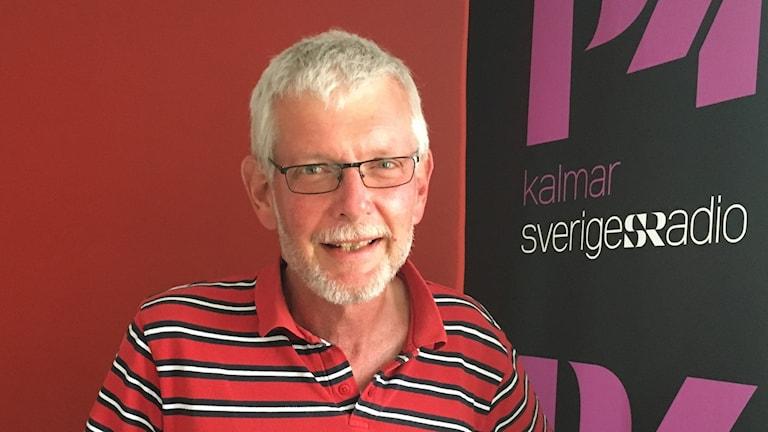Anders Åkesson står framför en röd vägg med P4 Kalmar-loggan