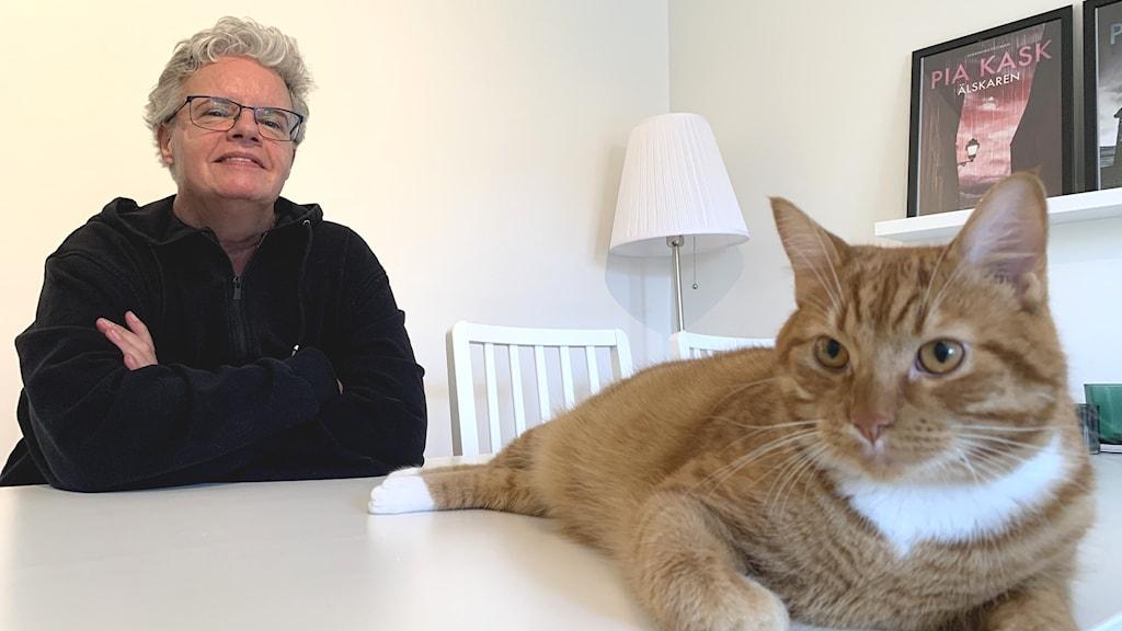 En kvinna sitter vid ett köksbord med en katt i förgrunden.