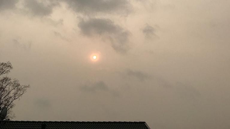 Solen på himlen döljs av mörka men tunna moln.