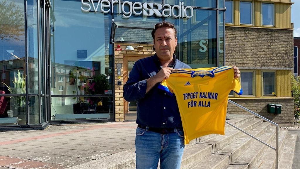 En man med en Sverigetröja i handen