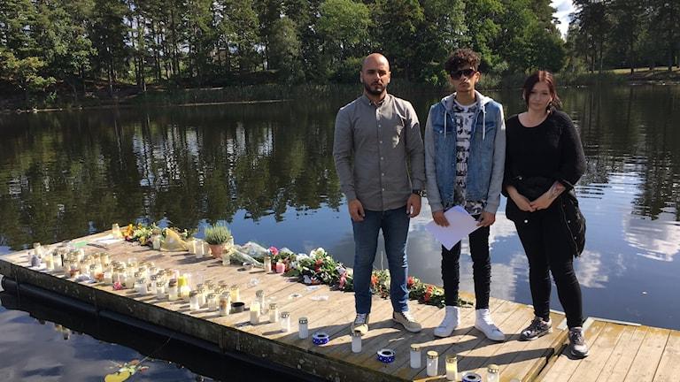 Familjemedlemmar till Saif Awes står på en brygga full av ljus och blommor vid Linneasjön.