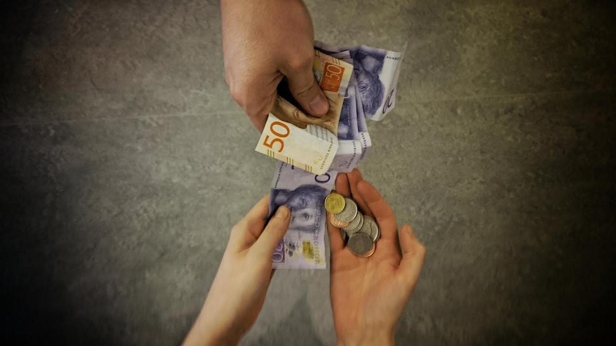 Händer håller i pengar.