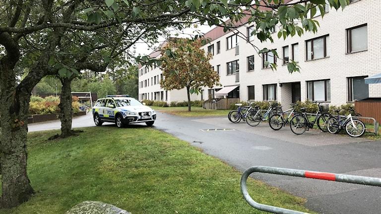En polisbil vid ett lägenhetshus.