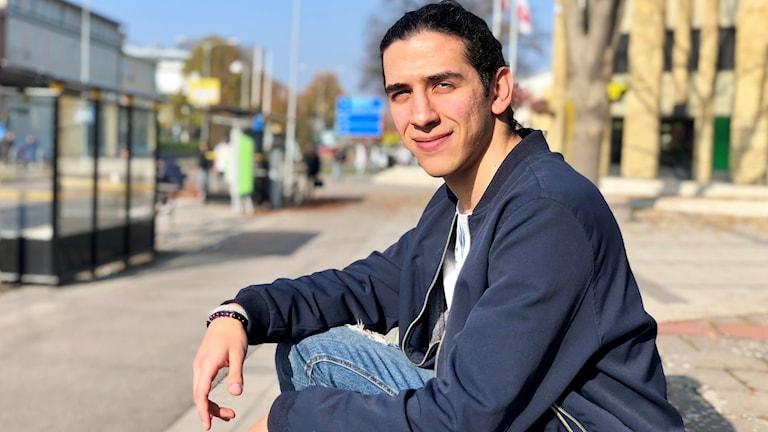 Bakri Wazzan sitter på att trappsteg framför en gul tegelbyggnad.