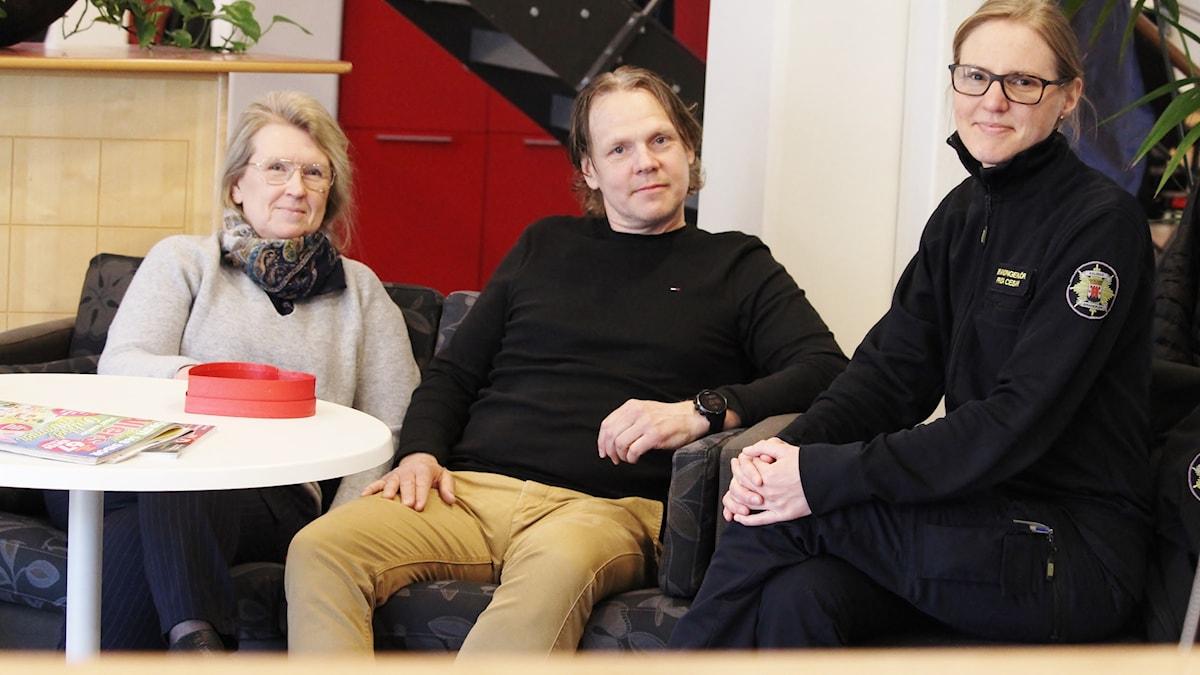 Tre personer, en man och två kvinnor, sitter i en soffgrupp.