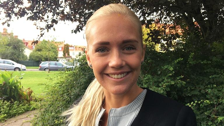 Porträttbild av Elsa Karlsson framför grönområde