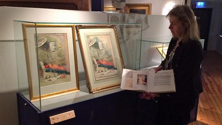 Barbro Johnsson Kalmar läns museum tittar på de två målningarna av Jenny Nyström.