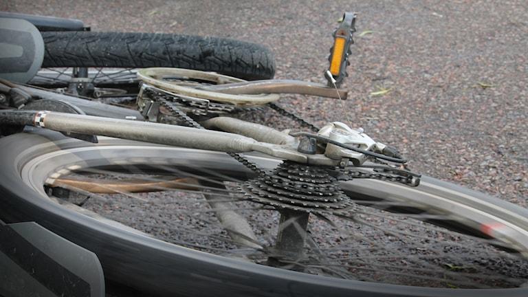 Cykel som ligger på asfalt.