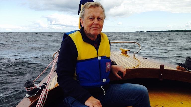 Thomas Johansson sitter i en motorbåt. I bakgrunden hav eller en stor sjö.
