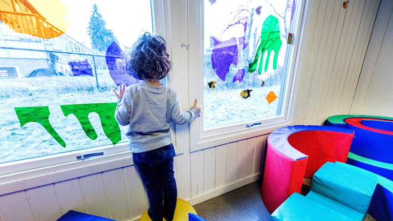 Barn står och tittar ut från fönster.