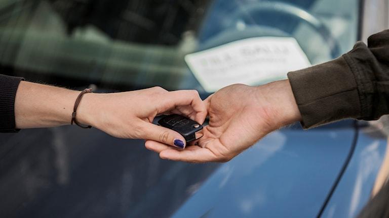 En hand räcker över en bilnyckel till en annan hand.