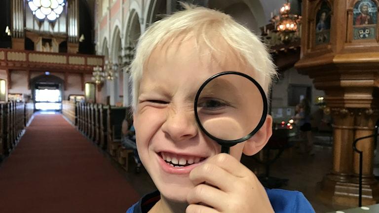 Pojke med förstoringsglas i handen.