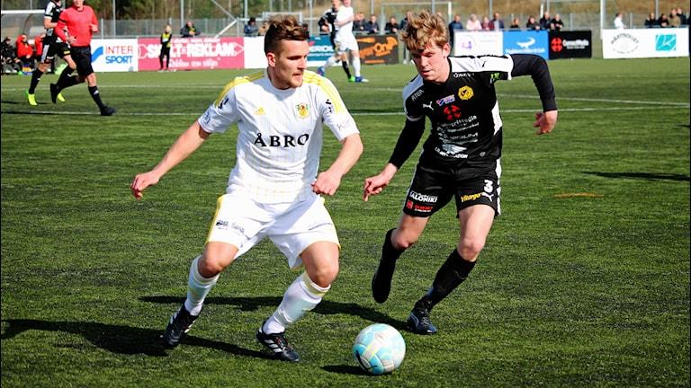 Två fotbollsspelare som kampar om bollen.