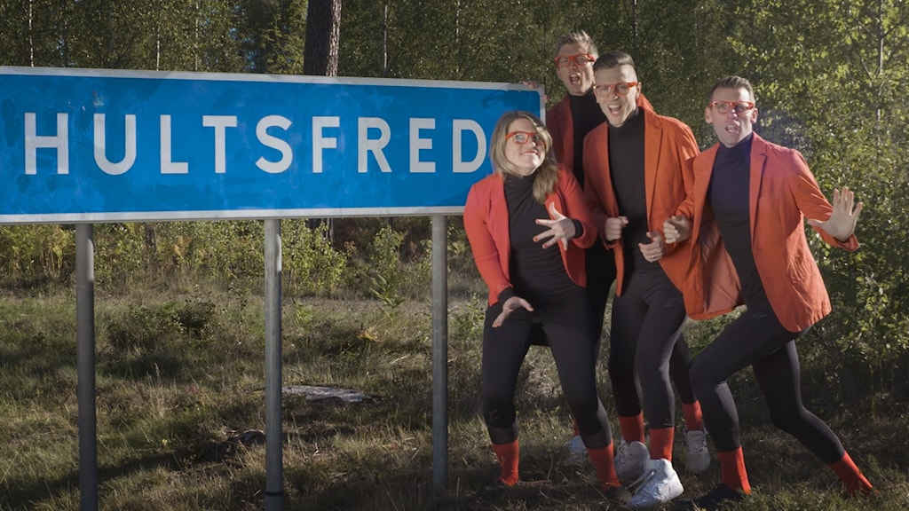 """Fyra personer framför en vägskylt med texten """"Hultsfred""""."""