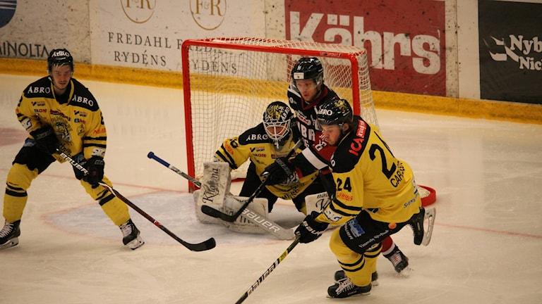 Hockeyspelare tampas om pucken.