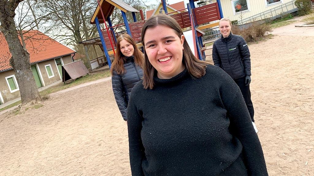 En kvinna i förgrunden och två kvinnor i bakgrunden.