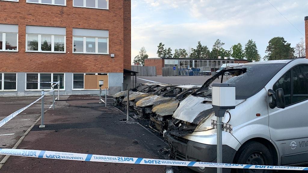 En parkering med flera bilvrak efter brand.