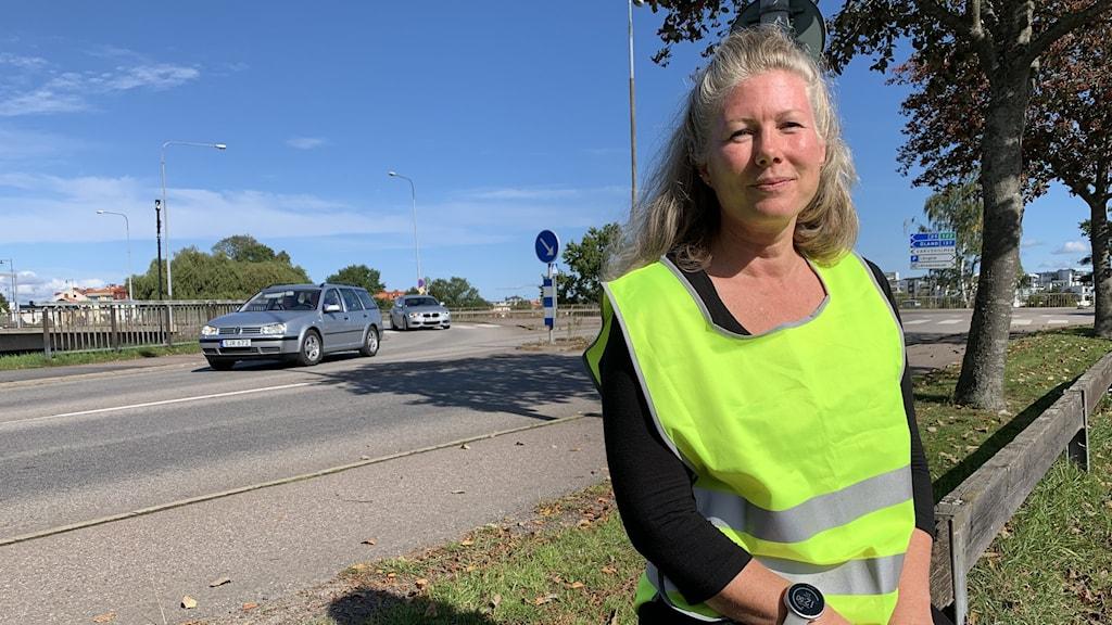 En kvinna lutar sig mot ett staket, bilar och väg i bakgrunden.