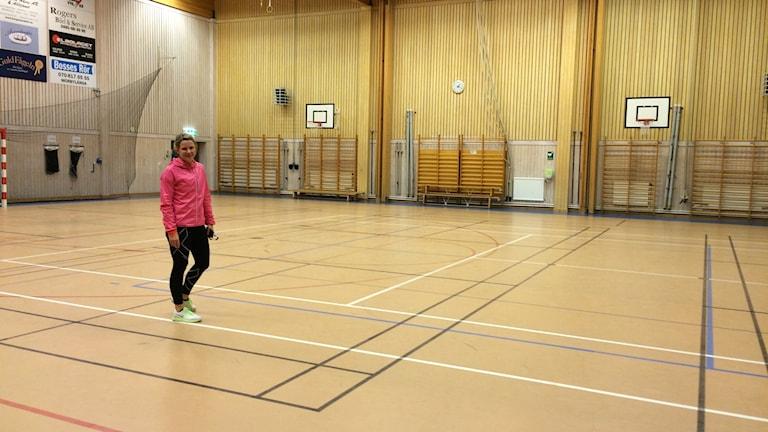 Kvinna med rosa jacka i en gymnastiksal