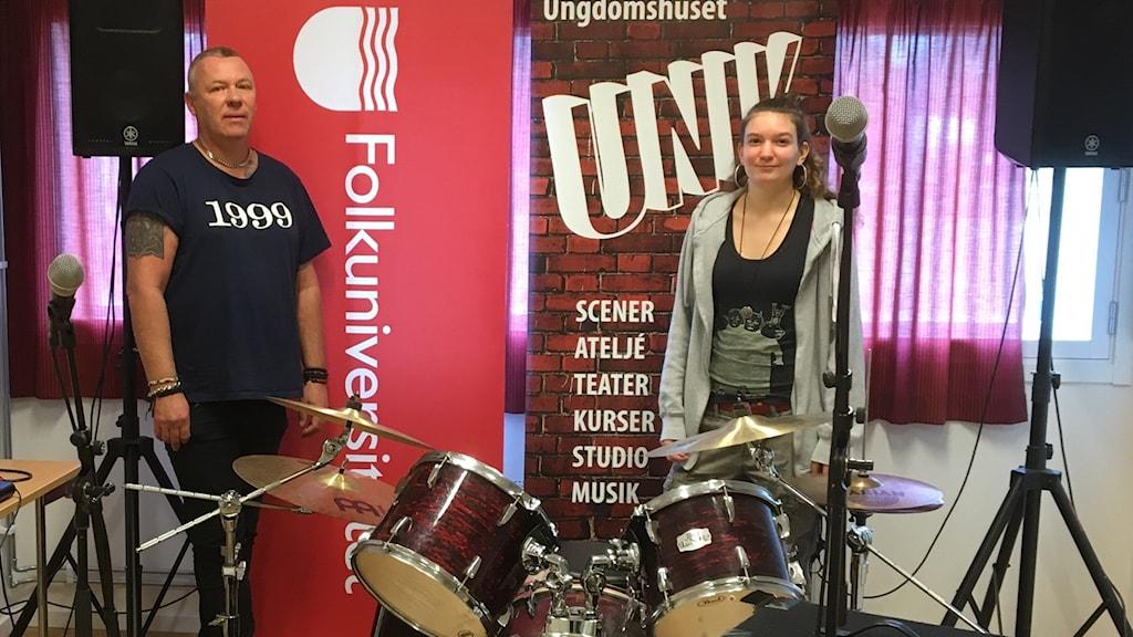 Två ungdomsledare i en replokal med trummor och gitarrförstärkare