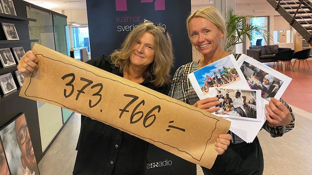 Bild på två kvinnor. Den ena håller en banderoll där det står 373766 kronor. Den andra håller i bilder från Världens Barn.