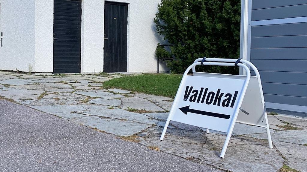 """En byggnad och en skylt med texten """"vallokal""""."""
