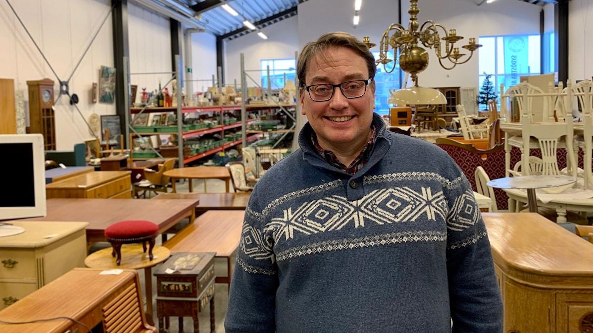 Daniel Johansson som jobbar på Kalmar auktionsverk står framför massa möbler i deras lokal.